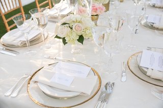 place-setting-with-gold-rimmed-charger-and-tan-napkin