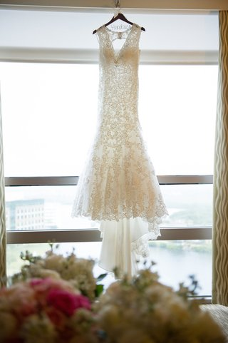 allure-lace-wedding-dress-hanging-in-window-of-hotel