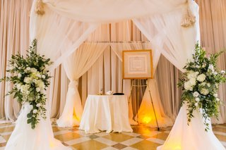 draped-white-ceremony-chuppah-with-floral-arrangements-of-white-flowers-and-greenery