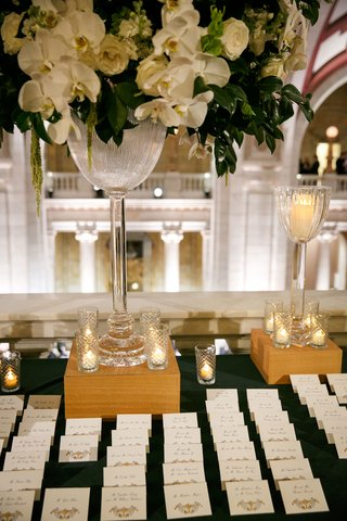 wedding-reception-escort-card-table-tall-arrangement-white-orchid-rose-greenery-gold-escort-cards