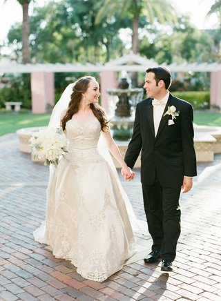 bride-groom-hold-hands-outside-venue-beaded-gown-florida-wedding-courtyard-photo-shoot-veil-bouquet