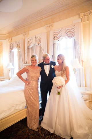bride-in-strapless-reem-acra-wedding-dress-with-bouquet-in-bridal-suite-with-mom-in-sparkly-dress