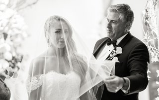 black-and-white-photo-of-father-of-bride-removing-veil-at-wedding-ceremony-touching-moment