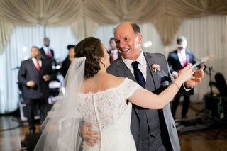 bride-in-an-off-the-shoulder-sottero-and-midgley-lace-dress-dances-with-father-in-grey-suit