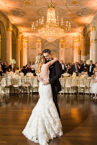 bride-and-groom-have-their-first-dance-at-biltmore-ballrooms-under-massive-chandelier-ines-di-santo