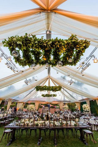 wedding-reception-greenery-ceiling-installations-with-glass-orbs-candles-white-drapery-tent-wood