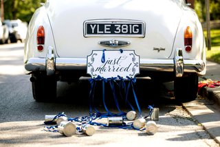 classic-white-car-with-just-married-sign-and-cans-trailing-behind-with-blue-ribbon