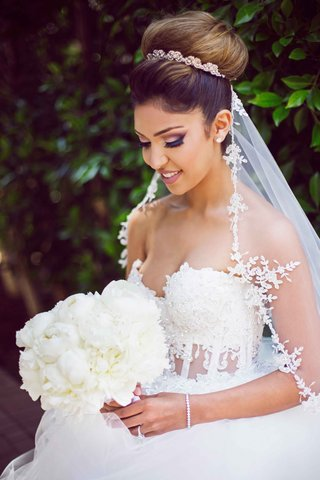 bride-smiling-bouquet-bold-makeup-eye-shadow-wedding-look-big-bun-up-do-white-bouquet
