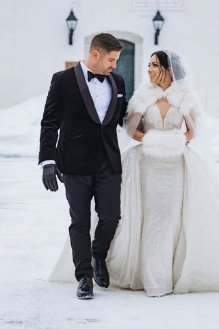 groom-in-tuxedo-bow-tie-and-black-gloves-bride-in-sparkle-dress-overskirt-fur-hand-muff-cape-hood