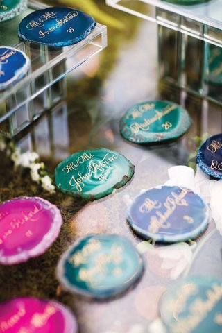 pink-teal-and-blue-agate-slices-used-as-escort-cards-with-gold-calligraphy
