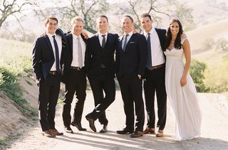 bride-and-groom-with-groomsmen-in-navy-suits-and-brown-shoes