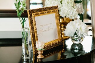gold-ornate-picture-frame-with-please-sign-our-guestbook-sign-on-table