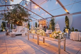 cocktail-hour-room-clear-top-tent-trees-on-both-sides-of-escort-card-table