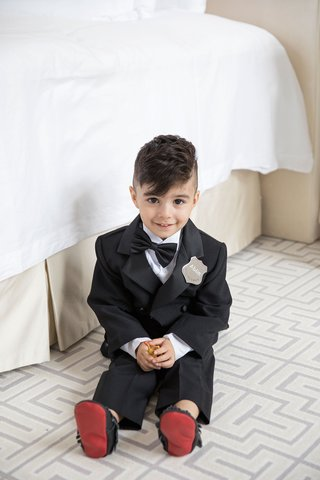 ring-bearer-with-cute-haircut-bow-tie-silver-badge-red-bottom-moccasins-tuxedo-mini-on-floor