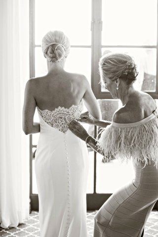 black-and-white-photo-of-mother-of-bride-helping-bride-put-on-ines-di-santo-wedding-dress