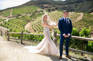 bride-in-pallas-couture-gown-with-blush-nude-lining-groom-in-navy-burberry-suit-vineyard-first-look