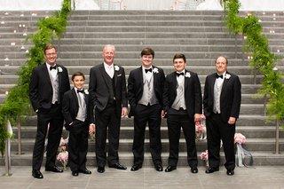 groom-groomsmen-charcoal-gray-pink-tie-in-front-of-steps-greenery-on-handrail