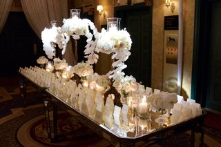 long-mirror-tables-with-escort-cards-white-and-tall-arrangements-of-orchid-hydrangea-flowers