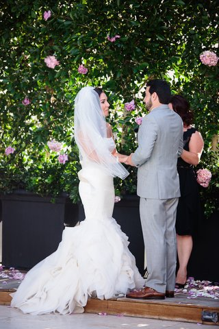 bride-in-a-fit-and-flare-vera-wang-dress-ruffled-skirt-and-groom-in-grey-suit-exchange-vows