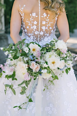 back-of-angel-sanchez-wedding-dress-buttons-flower-applique-vines-and-loose-bouquet-greenery