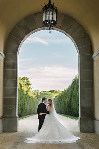 bride-and-groom-under-tall-archway-at-oheka-castle-gardens-cyprus-trees-clouds-sky