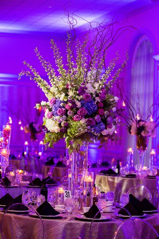 wedding-reception-round-table-decor-purple-lighting-clear-ghost-chair-tall-centerpiece-purple-flower