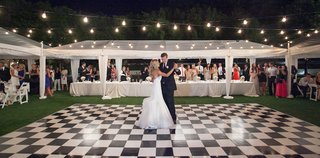 bride-in-a-strapless-hayley-paige-dress-dances-with-groom-in-black-tuxedo