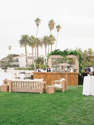wedding-reception-outdoor-bar-with-wood-lounge-area-greenery-tropical-theme