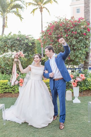 the-confused-millennial-off-shoulder-wedding-dress-after-ceremony-bouquet-grooms-arm-in-air-navy