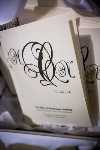 wedding-ceremony-program-with-the-couples-intials-written-in-calligraphy-gold-rhinestones