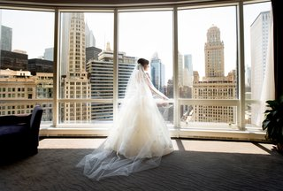 bride-looking-out-floor-to-ceiling-windows-in-chicago-bridal-suite-a-line-gown-and-veil-cathedral