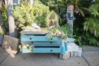 garden-wedding-with-a-vintage-light-blue-dresser-for-gifts-gold-birdcage-pink-white-flowers