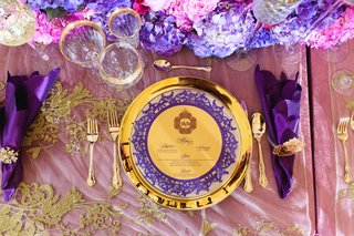 regal-themed-wedding-reception-shiny-gold-charger-plate-gold-menu-with-purple-border