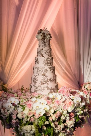 wedding-cake-on-table-with-white-orchid-pink-roses-drapery-blush-cake-with-gold-detailing-frosting