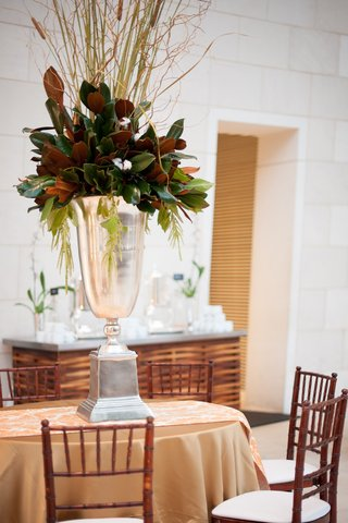 silver-urn-wedding-centerpiece-with-magnolia-leaves-and-cattail