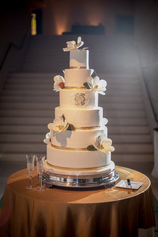 white-cake-with-gold-ribbons-monogram-and-magnolia-sugar-flower