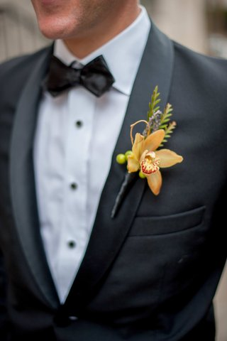 groom-in-tuxedo-with-orange-orchid-boutonniere