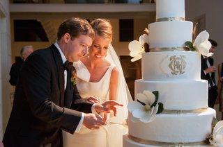 bride-and-groom-cut-magnolia-and-monogram-cake