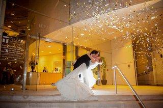 groom-dips-bride-as-confetti-blows-outside-museum-venue