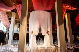 tall-white-fabric-chuppah-with-clear-chairs-surrounding