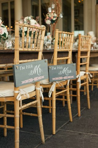 signs-that-say-im-her-mr-and-im-his-mrs-hanging-from-the-back-of-couples-chairs-at-the-reception