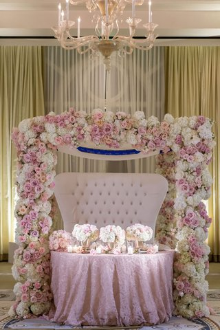 wedding-reception-ballroom-sweetheart-table-tufted-settee-pink-white-flowers-pink-linen-chandelier