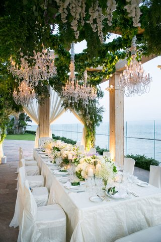 wedding-reception-dinner-table-one-table-intimate-wedding-chandeliers-greenery-white-lavender-flower