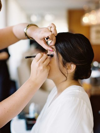 bride-with-updo-getting-eye-liner-put-on-by-makeup-artist-in-white-robe
