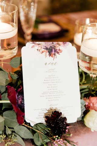 wedding-menu-with-die-cut-border-purple-amber-gold-flower-print-motif-on-table-gold-lettering
