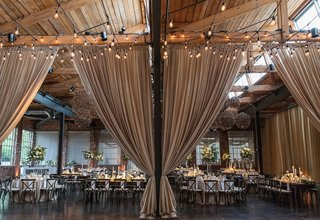 rustic-elegant-reception-with-tan-drapery-dividing-the-room