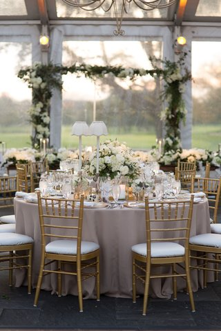 wedding-reception-clear-tent-white-table-lamps-gold-chairs-white-greenery-centerpiece-design