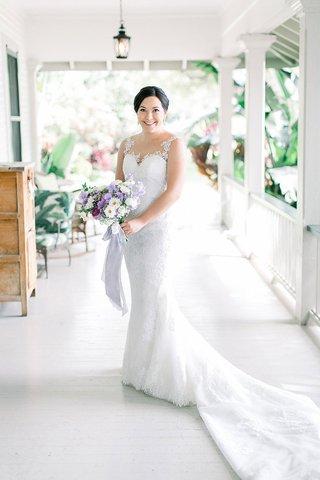 bride-in-illusion-wedding-dress-lace-with-sheer-neckline-purple-bouquet-plantation-porch-hawaii