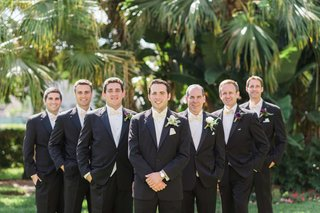 groom-groomsmen-triangle-pose-smiling-white-green-boutonnieres-florida-wedding-outside-classic
