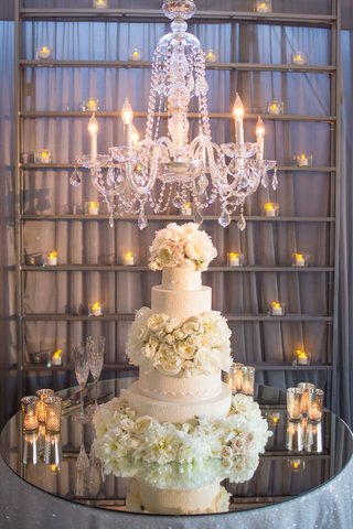 extravagant-wedding-cake-with-garden-roses-and-peonies-displayed-on-mirrored-table-under-chandelier